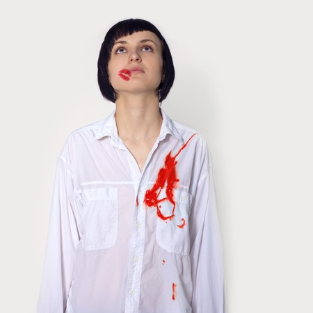 girl with lipstick trace and heart wound in white shirt in studio photo