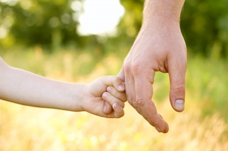trust people: father lead by the hand son outdoor