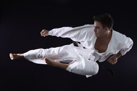 martial arts: karate man champion of the world on black background studio shot