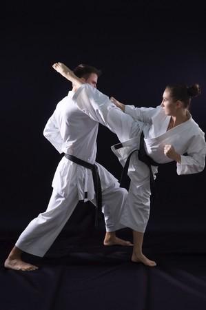 patada: combates par de karate - campeones del mundo - el estudio de fondo negro filmado  Foto de archivo