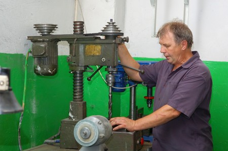 hábil: skilled labourer with drilling machine in factory