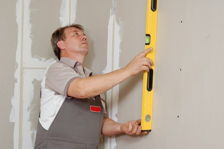 handtools: man with level make renovation indoor Stock Photo