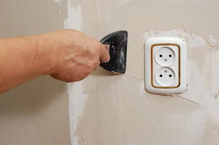 home improvement - man stop up wall near socket photo