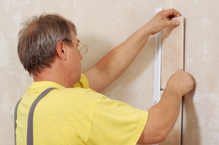 tiling - man installs ceramic tile  photo