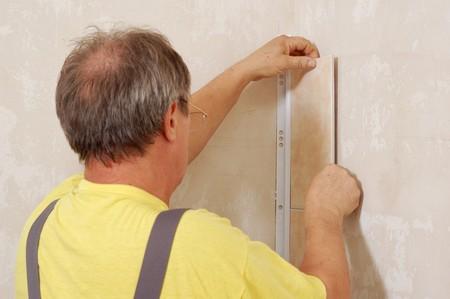 tiling - man installs ceramic tile Stock Photo - 7842716
