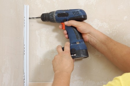 man with hand electric drill make renovation indoor photo