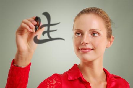 beautiful woman writing hieroglyph life over ligth green background photo