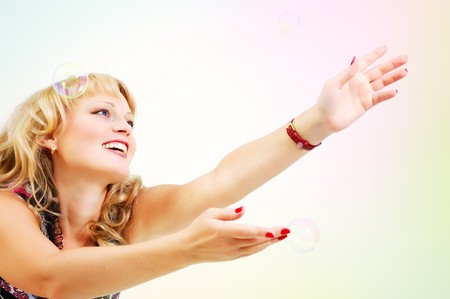 beautiful happy woman reach for soap bubbles isolated on white background photo