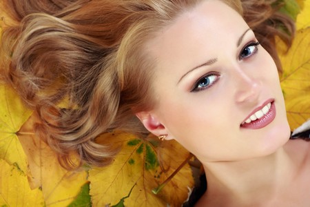 beautiful woman with maple leaves studio shot photo