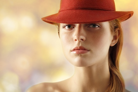 elegant young woman with red hat over light background photo
