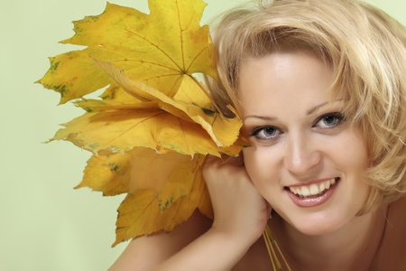 beautiful woman with maple leaves over light green backgroound Stock Photo - 8385126