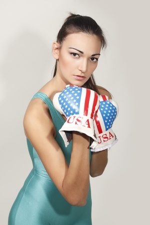 boxing young woman isolated on gray background photo