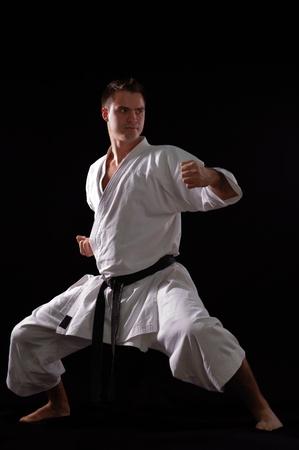 art activity: karate man champion of the world on black background studio shot