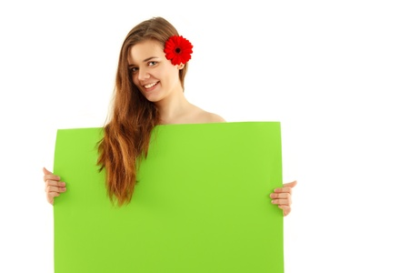 spa happy teenager girl with red flower in long hair holding green empty banner isolated on white background photo