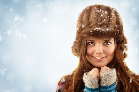 teennager girl pretty smiling on winter snow blue background photo