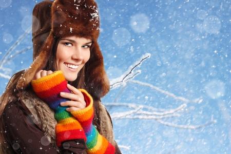 ropa de invierno: chica adolescente bastante sonriente sobre fondo de nieve azul de invierno