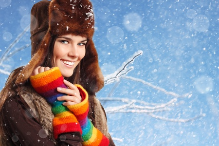 winter woman: teenager girl pretty smiling on winter snow blue background Stock Photo