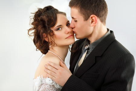 groom kissing young beautiful bride photo