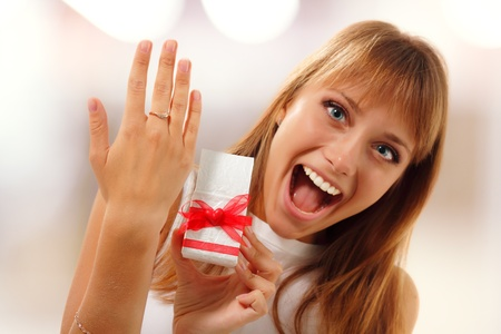 happy cute girl is showing valentine gift engagement ring on her finger photo