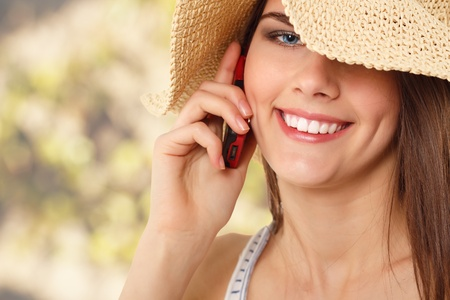 summer teen girl cheerful in straw hat calling mobile phone over nature background photo