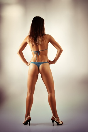woman beautiful back athletic muscular in swimsuit and heel-strap full length photo
