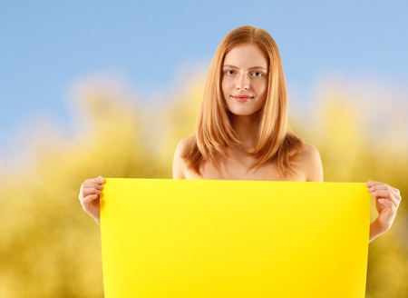 woman holding blank yellow banner over nature background Stock Photo - 10460881