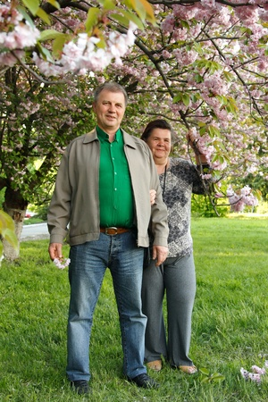 mature couple cheerful hug in spring garden photo