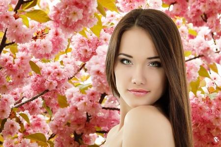 beautiful girl face: teen girl beautiful cheerful enjoying over spring Japanese cherry tree background Stock Photo