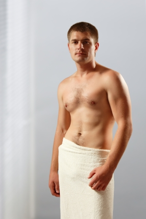 body conscious: man young handsome athlete with bath towel  Stock Photo