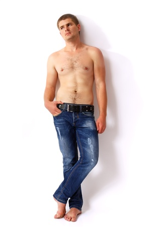 muscular men: man young handsome athlete with with blue jeans barefoot isolated Stock Photo