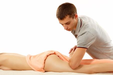 nalga: masajista hace masaje anticelul�tico mujer joven aislado en fondo blanco
