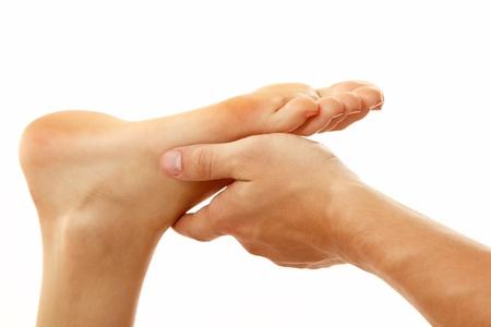leg massage: massage foot female close-up isolated on white background Stock Photo