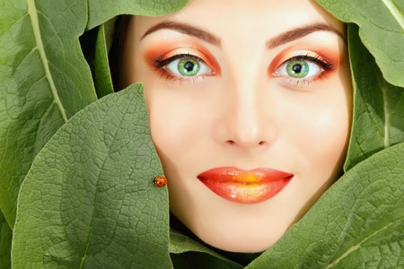 sexiness: woman beauty face with green leaves with ladybird frame