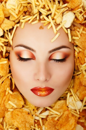 woman beauty face victim of unhealth eating fast food potato chips rusk frame photo
