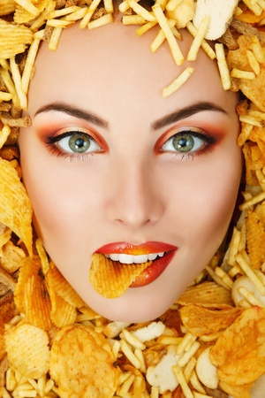 unhealth: woman beauty face with unhealth eating fast food potato chips rusk frame