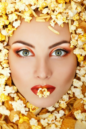 woman beauty face with unhealth eating fast food popcorn potato chips rusk frame photo
