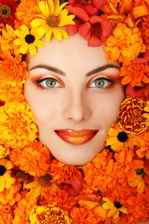 woman beauty face with orange flowers frame  photo