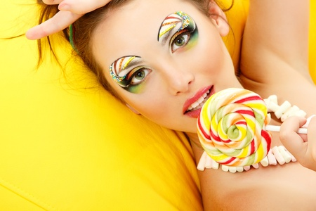 woman licks candy with beautiful make-up photo
