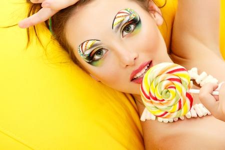 woman licks candy with beautiful make-up photo