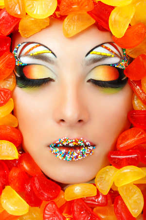 sexy mouth: woman sweet candy caramel with beautiful make-up young attractive