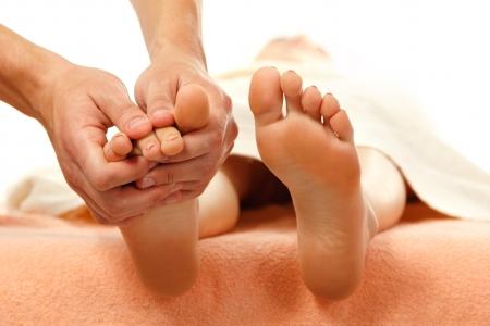 masaje: masaje de pies femeninos de cerca aisladas sobre fondo blanco