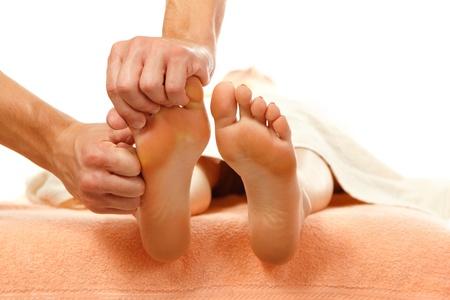 reflexologie: massage des pieds femme close-up isolé sur fond blanc