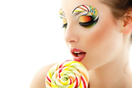 candy background: woman licks candy with beautiful make-up isolated on white background Stock Photo
