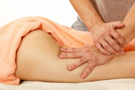 nalga: masajista hace masaje anticelulítico mujer joven aislado en fondo blanco