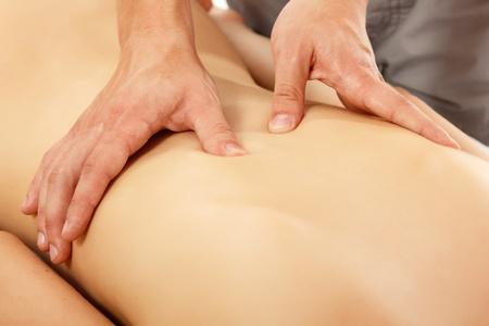 human being: hands of masseur massaging woman young beautiful