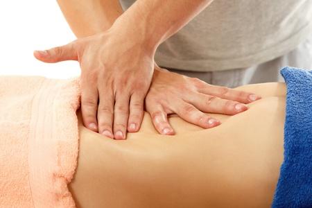 vientre femenino: masajista hace que la mujer del vientre de masaje joven aislado en fondo blanco
