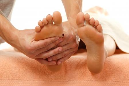 masoterapia: masaje de pies femeninos de cerca aisladas sobre fondo blanco