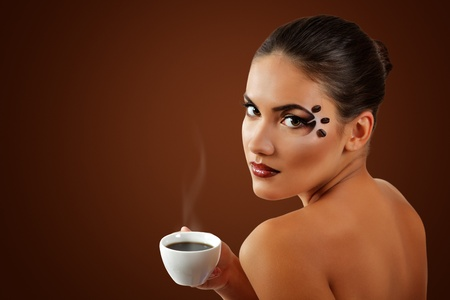 woman drinking coffee with beautiful make-up isolated on brown background photo