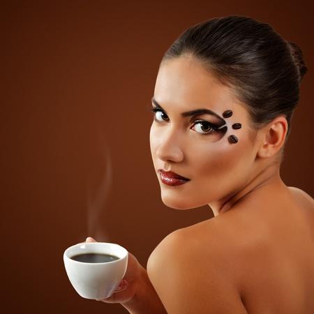 mujer tomando cafe: café mujer bebiendo con un hermoso maquillaje aislada en el fondo de color marrón Foto de archivo