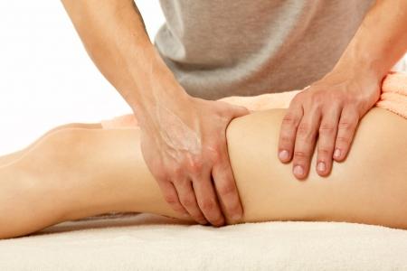 massage jambe: masseur fait massage anticellulite femme jeune femme isol�e sur fond blanc Banque d'images